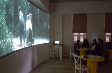 תמונה של אנשים צופים במיצג המרכזי בבית שיח נשים - סרט המוקרן על גבי מסך גדול על הקיר